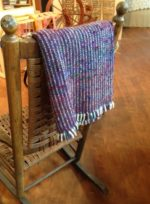 A lap blanked made from a mixed warp and a recycled sari silk weft.