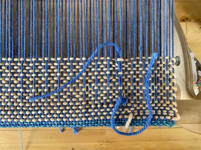 pinning supplementary warp end to the cloth
