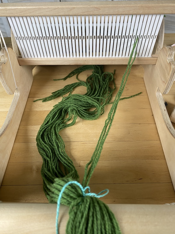 warp secured to front of the loom, overhand knot untied, partially threaded rigid heddle