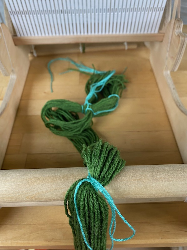 warp tied to the front beam with the cross facing the rigid heddle