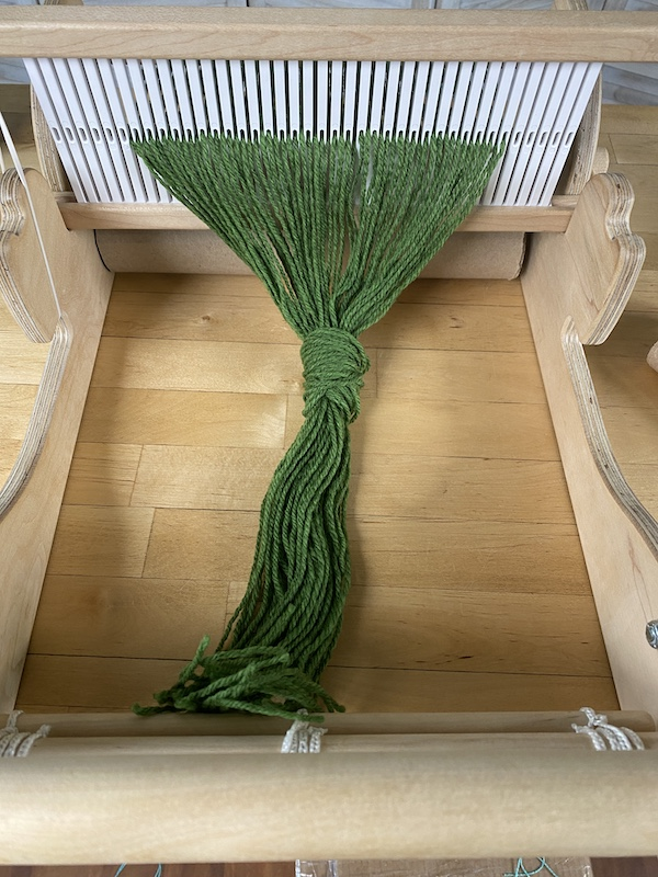 warp untied from the front apron rod with a loose overhand knot tied in the warp about six inches from the end